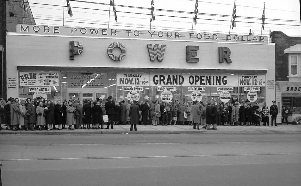 We once had three supermarkets at Danforth and Woodbine, though the Valumart site was NOT one of them. We had Red & White, in what is now Value Village. Loblaws where we have Scotiabank, and we had Power (and later Busy Bee) where we now have Carmelina. This was the lineup for the grand opening at Power on Nov. 12, 1953.